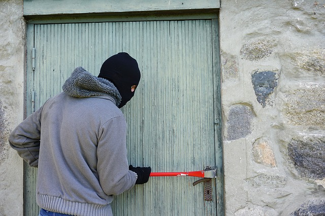 image of man breaking into house