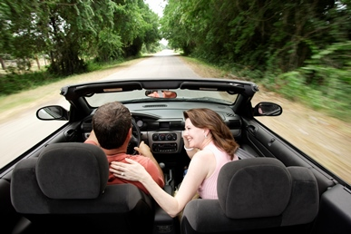 image of couple driving in a convertible